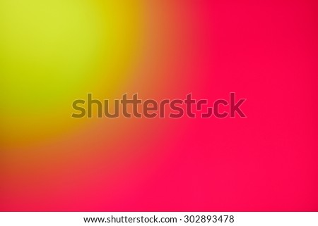 Abstract yellow blur against shiny bright red background. Yellow sun in the corner of red sky. An out of focus yellow ball against a red wall.