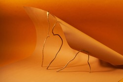 Abstract yellow-brown background for designers, curved paper and soft light, poppy branch with shadow on paper.