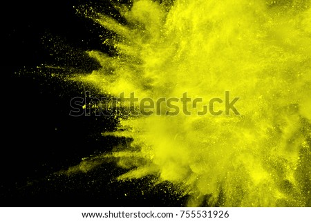 abstract yellow dust explosion on  black background.abstract yellow powder splattered on dark  background. Freeze motion of yellow powder splash.