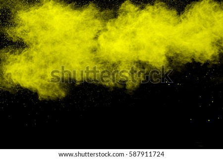 abstract yellow powder explosion on  black background.abstract yellow powder splatted on black background. Freeze motion of yellow powder exploding. #587911724