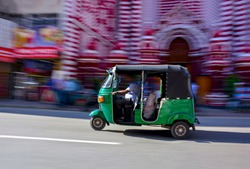 Abstracted Panning Photography Of A Three Wheeler In Front Of Red Mosque In Colombo, Sri Lanka. Tuk Tuk Can Be Found On All Roads In Sri Lanka That Transporting Locals, Foreigners, Or Freights
