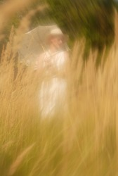Abstraction. An unrecognizable girl in a long white dress, hat and solar umbrella, walking among tall yellow bushes. In defocus. The background is blurred. Bright sunny summer day. Outdoors. Nature.
