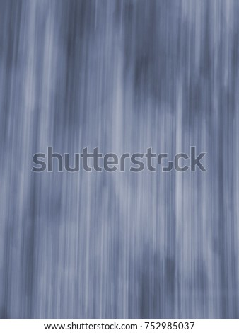 Abstraction of water falling in speed. Waterfall or rain shown with vertical blue lines for background or wallpaper. Fast motion in monochromatic color. #752985037