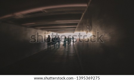 Abstraction - people walk in a dark tunnel to meet a bright light (exit). Glare.