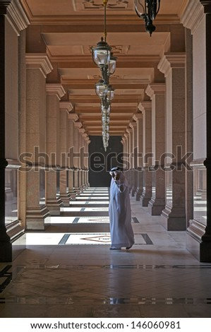 ABU DHABI, UAE - MARCH 17, 2010: Man walking outside of Emirates Palace hotel on March 17, 2010. Emirates Palace is a luxurious and the most expensive 7 star hotel designed by John Elliott RIBA.