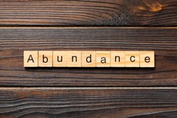 Abundance word written on wood block. Abundance text on wooden table for your desing, Top view concept.