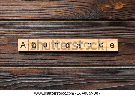 Abundance word written on wood block. Abundance text on wooden table for your desing, Top view concept. Stock photo ©