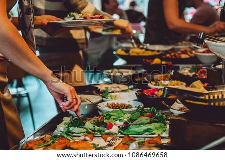Abundant food table, brunch in coffee shop, people eating food