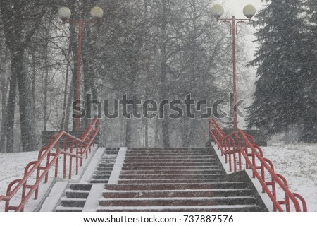 abundant precipitation in the form of wet snow during a violent storm against the background of a city staircase made of concrete #737887576