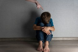Abused boy hiding his face into his knees, adult's hand with pointing finger is above his head. Home violenceand punishment
