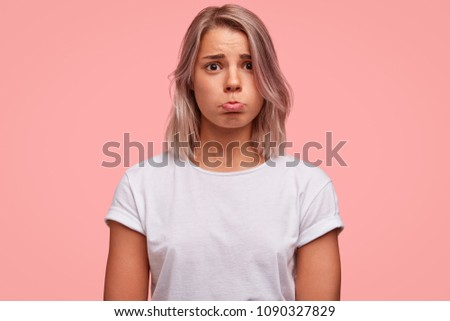 Abused pretty female curves lower lip, being offended during quarrel, looks with sorrowful miserable expression, wears casual white t shirt, isolated over pink background. Disappointed unhappy woman