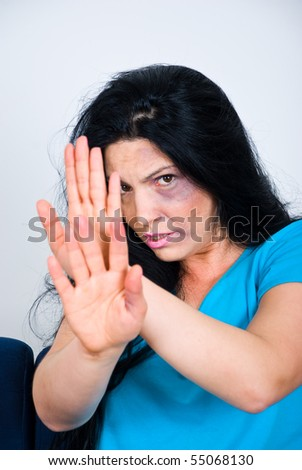 Abused scared woman  with bruises on face sitting  and showing stopping hands