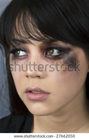 Abused woman crying with makeup smeared