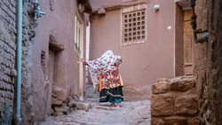 Abyaneh, Iran - May 2019: Unidentified woman with traditional Persian clothes resting by a narrow road