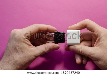 AC and DC adapters in men's hands. The male connects the black wall adapter for Europe and the white adapter for the US. Top view, pink background. Photo stock ©