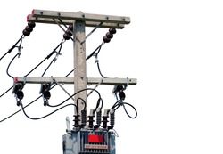 AC high-voltage power transformer. Electrical energy transfer to end users through distribution transformer on concrete pole changing high voltage to low voltage isolated on white background.