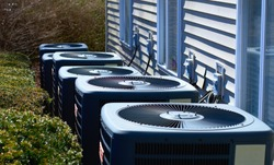 AC units outside of an apartment complex. Cooling units are outside.