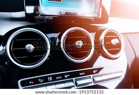 AC ventilation deck in luxury modern car Interior. Modern car black leather interior. Natural wood panel. Perforated black leather. Car interior. Car inside with sun rays Foto d'archivio ©