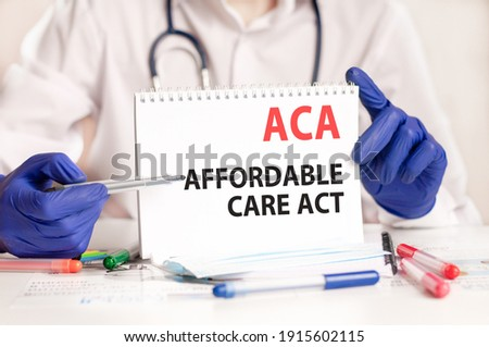 ACA card in hands of medical Doctor. Doctor's hands in blue gloves holding a sheet of paper with text ACA - short for Affordable Care Act, medical concept. Imagine de stoc ©