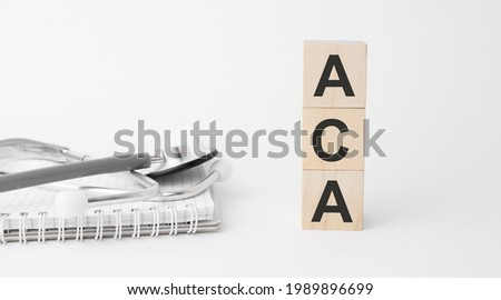 aca inscription on wooden cubes isolated on white background, medicine concept. Nearby on the table are a stethoscope and pills. Imagine de stoc ©