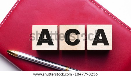 ACA is made up of wooden cubes that stand on a burgundy notebook near the pen. Business concept Imagine de stoc ©