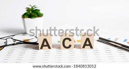 ACA written on a wooden cube on chart background Imagine de stoc ©