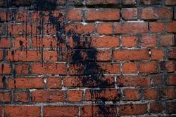 acade of a brick wall. Red brick masonry. Black paint wall