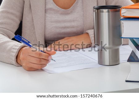 Academic teacher during writing an article with a coffee and books
