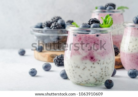 Photo of Acai berry and chia seed pudding with blueberries and blackberries in glass jars on a light white table. Copy space, horizontal image, front view