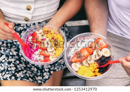Acai bowl and pitaya dragonfruit smoothie healthy breakfast bowls young friends eating together. Couple man and woman eating sitting outside in park for lunch break. Closeup on food.