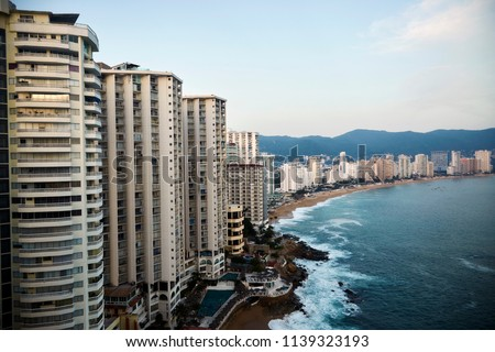 Acapulco bay with its characteristic line of hotels in front of a tiny beach line with a beautiful blue ocean on a sunny summer day #1139323193