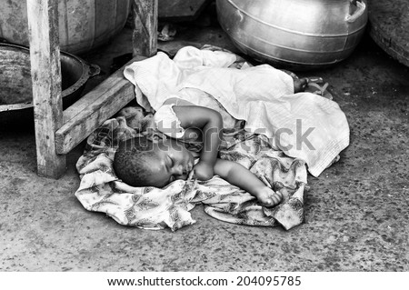 ACCARA, GHANA - MAR 2, 2012: Unidentified Ghanaian girk sleeps on the ground in black and white. Children of Ghana suffer of poverty due to the unstable economical situation #204095785