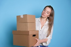 Accept a parcel, happy young woman holding a stack of cardboard boxes, portrait on a blue background