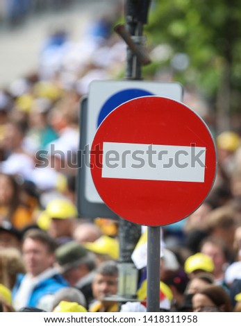 Access denied road sign with a large mass of people in the background - social or mass control #1418311958