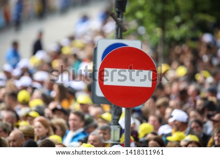 Access denied road sign with a large mass of people in the background - social or mass control #1418311961