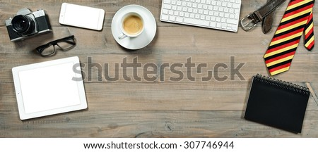 Accessories and digital gadgets for man. Tablet pc, keyboard, camera, phone and coffee on wooden table. Working station mock up