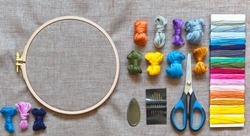 Accessories for embroidery: needles, set of colored mouline threads, needle threader, scissors and natural linen canvas on wooden hoop for stitch or cross-stitch embroidery. Copy space, flat lay