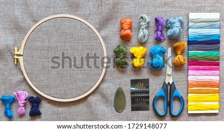 Accessories for embroidery: needles, set of colored mouline threads, needle threader, scissors and natural linen canvas on wooden hoop for stitch or cross-stitch embroidery. Copy space, flat lay  Photo stock ©