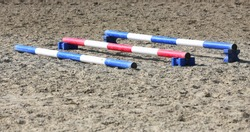 Accessories for horse trainings and events in rural equestrian training centre. Image of an empty training field. Barriers for schooling horses as a background.