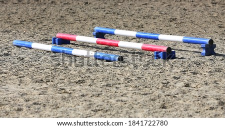 Accessories for horse trainings and events in rural equestrian training centre. Image of an empty training field. Barriers for schooling horses as a background. Сток-фото ©