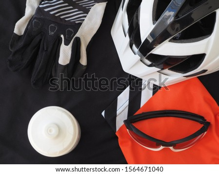 ACCESSORIES FOR MOUNTAIN BIKE. Black men's jersey, eyeglasses, gloves and white bicycle helmet. sport accessories, sport equipment. Top view.