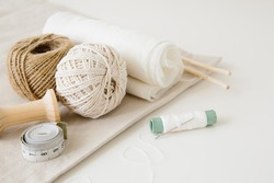Accessories for sewing and handicraft: woolen threads, fabric cuts, needle and measuring tape. Sewing and needlework concept.