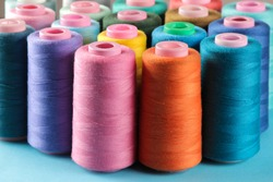 Accessories for sewing and needlework. Many multi-colored spools of thread. Bobbins with colored thread