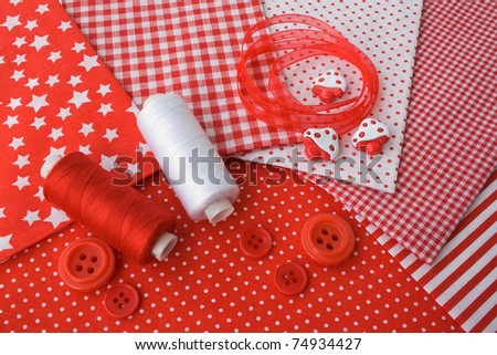 Accessories for sewing: threads, fabric, buttons in red-white color