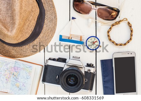 Accessories for travel. Different objects on wooden background. Passport, photo camera, smart phone, sunglasses and travel map. Top view. Tourism, holidays and tourism concept #608331569