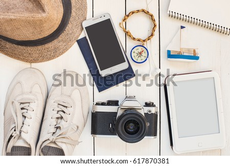 Accessories for travel. Different objects on wooden background. Passport, photo camera, smart phone, shoes, sunglasses and ebook reader . Top view. Tourism, holidays and tourism concept #617870381