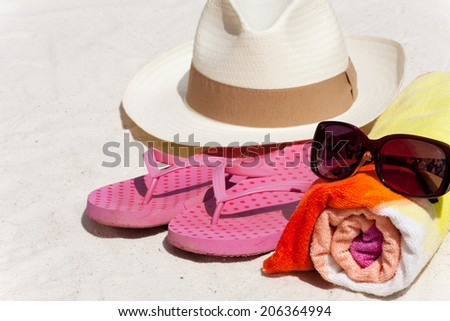 Accessories how Sunglasses, Beach Towel, Straw Hat and Flip-Flops for the Beach Holiday