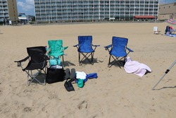 Accessories of the beach goer, chair, flip flops towel and beach bag with other items on a sandy beach