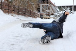 Accident danger in winter. A man has slipped and has fallen down