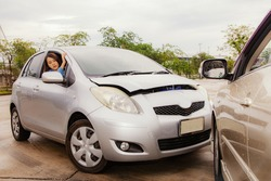 Accident during driving and car insurance concept : Beautiful Asian woman driving a bronze car gets into a road accident and collides with a speeding car because she can't brake and has a panic face.